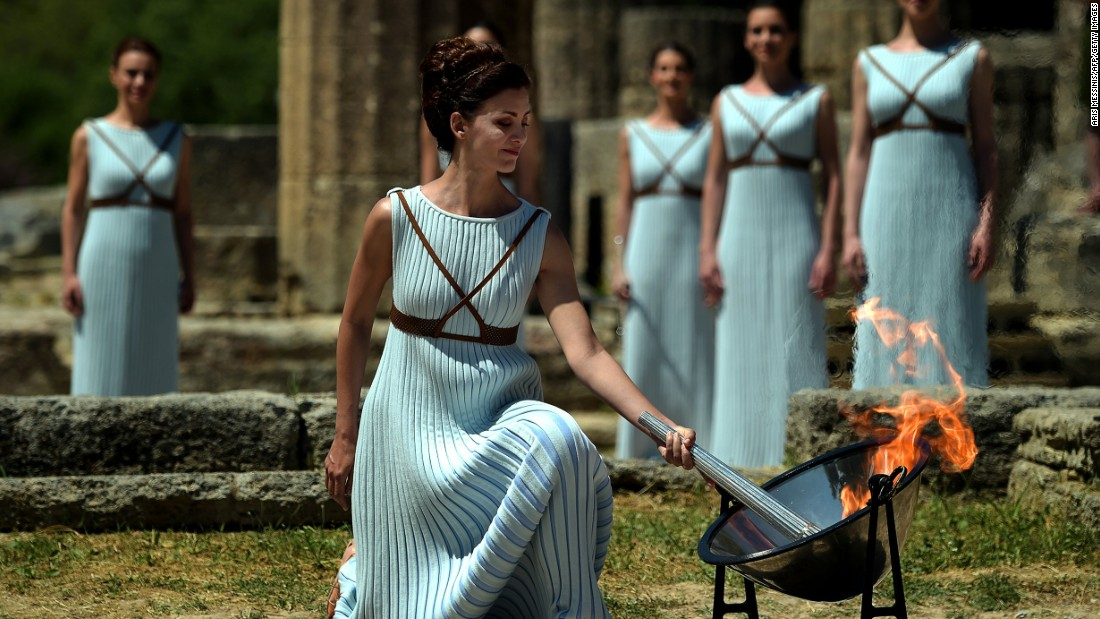 The Olympic flame is back: Greek actress Katerina Lechou performs the role of the high priestess as she lights the Olympic flame at the Temple of Hera at the site of ancient Olympia.