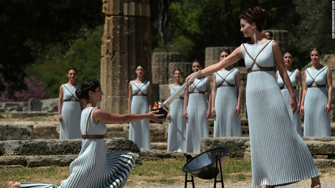 Lechou passes the Olympic flame into a small ceramic bowl. The ceremony was performed at the site where the Olympics were born in 776 BC and remained for 12 centuries.