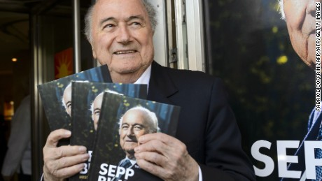 FIFA's ex-president Sepp Blatter poses with a copy of his biography.