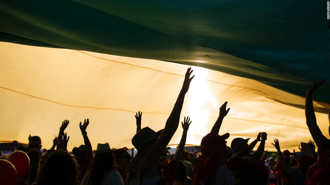 "Pro-government demonstrators raise their hands under a giant flag near congress as lawmakers vote on whether or not to impeach <a href=""http://www.cnn.com/2016/04/19/americas/brazil-dilma-rousseff-speaks/"" target=""_blank"">President Dilma Rousseff</a> in Brasilia, Brazil, on Sunday, April 17. The vote will determine whether the impeachment proceeds to the Senate. Rousseff is accused of violating Brazil's fiscal laws to shore up public support amid a flagging economy."