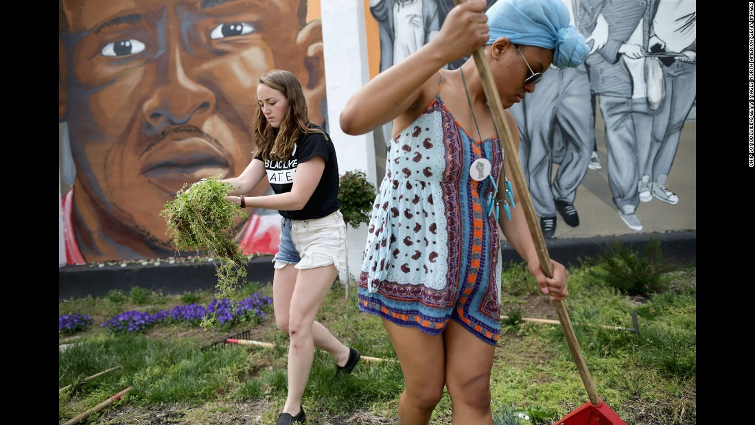 On Tuesday, April 19, Loyola University students Kate Spence, left, 21, and Kassina Dwyer, 18, work to clear and landscape the garden in front of a large memorial mural of Freddie Gray one year after he died in Baltimore, Maryland. Freddie Gray died in the hospital one year ago after suffering a severed spinal cord while in the custody of Baltimore Police, setting off weeks of demonstrations that boiled over into rioting, looting, arson and violence on April 27, 2015. <br />