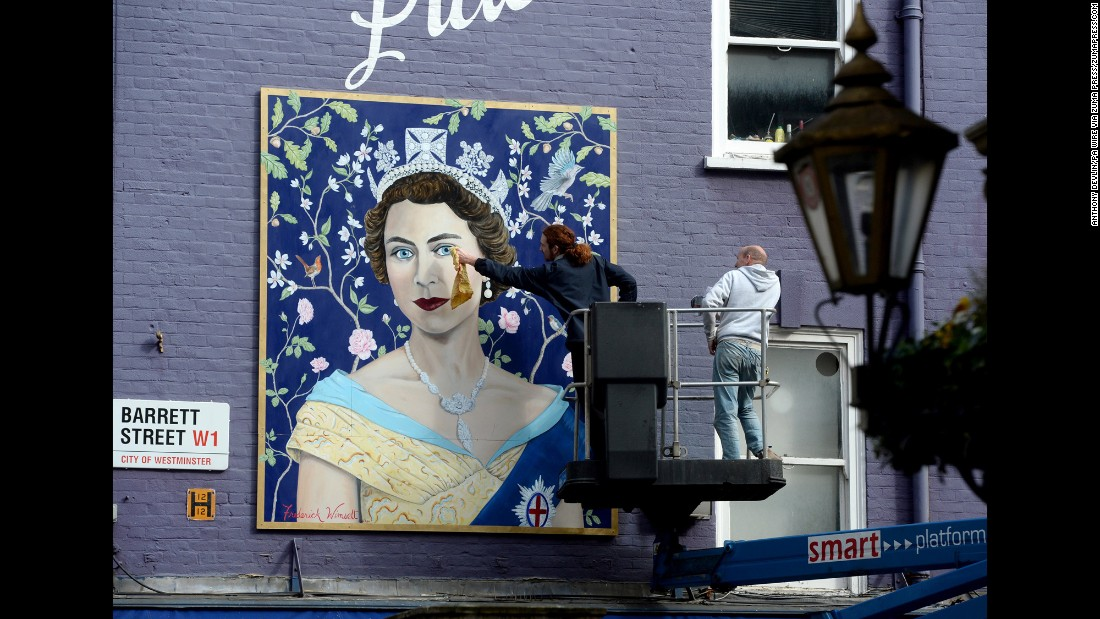 "Workmen on Tuesday, April 19, install a newly commissioned portrait by muralist Frederick Wimsett of <a href=""http://www.cnn.com/2016/04/20/europe/queen-elizabeth-90/index.html"" target=""_blank"">Queen Elizabeth II</a> at St. Christopher's Place in London, offering shoppers an opportunity for a ""selfie"" with the Queen to celebrate her 90th birthday."