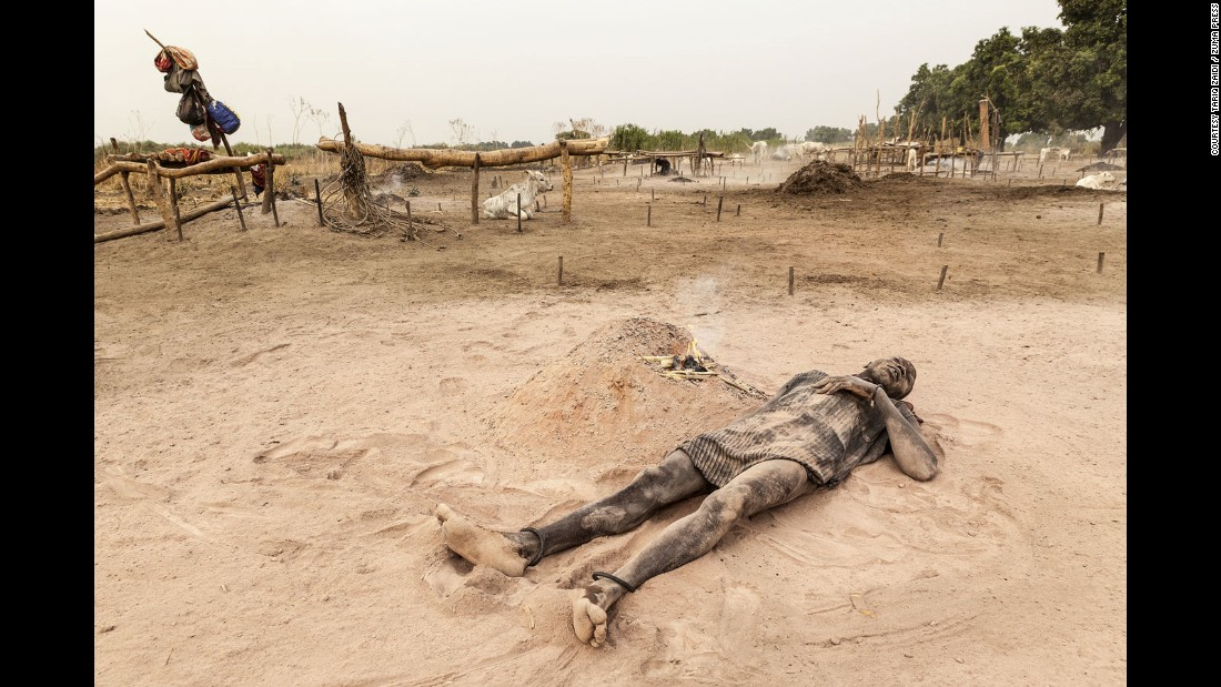 A Mundari man relaxes in the soft, peach-colored ash and dust of a dung fire. Zaidi says its consistency is close to that of talcum powder, and is applied to the skin as a means of sun protection.