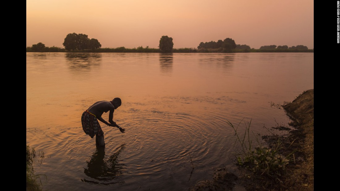 A Mundari tribeswoman washes herself in the Nile at sunset. Bathing in the river is a rare site according to the photographer.