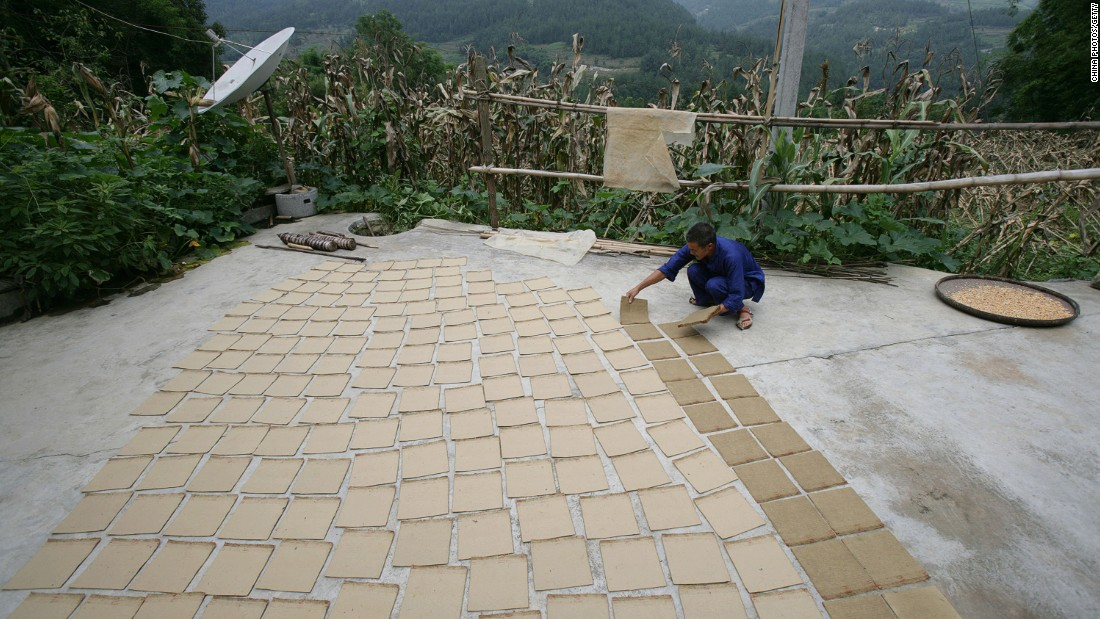 A worker arranges sheets of handmade bamboo paper on the ground to dry at a papermaking workshop in the village of Tianwan in China. The paper is mainly used for packaging of local farm products.