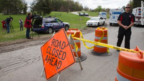 Media and emergency personnel stand at the perimeter of a crime scene as investigation vehicles drive up Union Hill Road, Friday, April 22, 2016, in Pike County, Ohio. Shootings with multiple fatalities were reported along a road in rural Ohio on Friday morning, but details on the number of deaths and the whereabouts of the suspect or suspects weren't immediately clear. The attorney general's office said a dozen Bureau of Criminal Investigation agents had been called to Pike County, an economically struggling area in the Appalachian region some 80 miles east of Cincinnati. (AP Photo/John Minchillo)