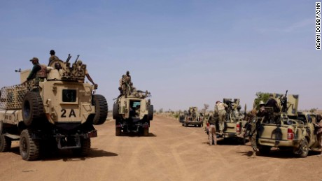 A heavily armored convoy of Nigerian Army personnel travel down the dusty road leading to the Sambisa Forest.
