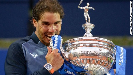Rafael Nadal takes his customary bite out of the Barcelona Open trophy after regaining it from Japan's Kei Nishikori.