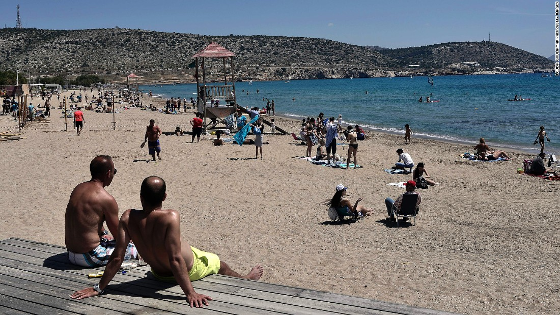 People sunbathe on a beach near Athens, Greece, on Sunday, April 24.