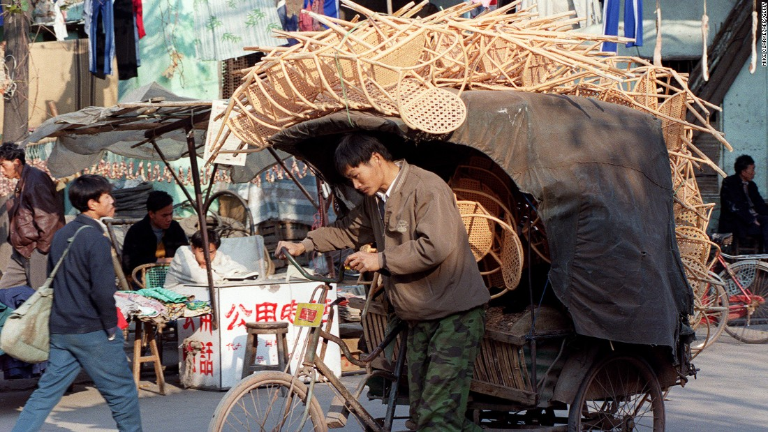 A man cycles a cart loaded with chairs made from bamboo for market in Guangzhou City, China. Bamboo is popular for furniture, and it's grown in the outskirts of the city.