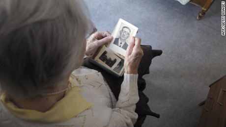 A woman, suffering from Alzheimer's desease, looks at an old picture on March 18, 2011 in a retirement house in Angervilliers, eastern France.   AFP PHOTO / SEBASTIEN BOZON (Photo credit should read SEBASTIEN BOZON/AFP/Getty Images)