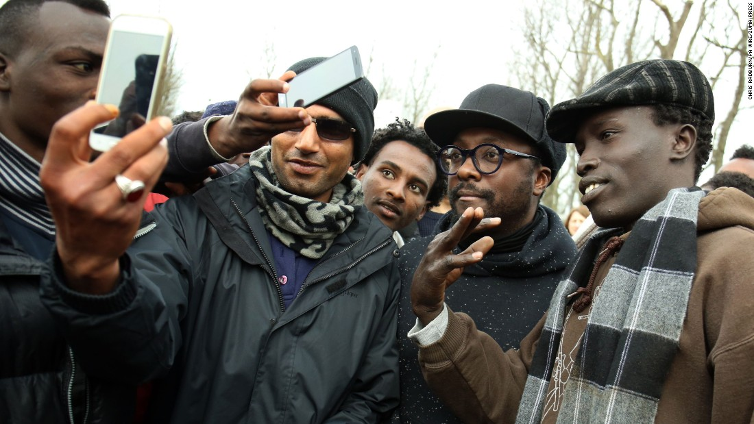 Musician will.i.am, second from right, visits a migrant camp in Calais, France, on Wednesday, April 13.