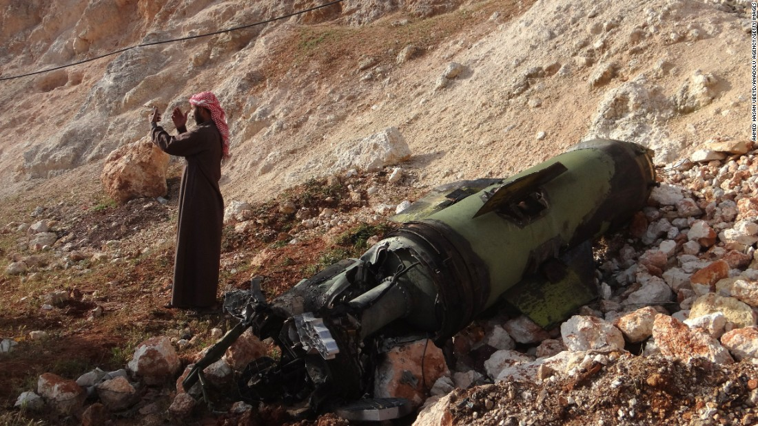A man in Aleppo, Syria, takes a selfie in front of a missile that landed in a field on Tuesday, April 26.