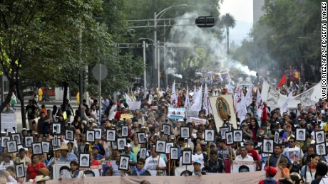 The parents of 43 missing students from Ayotzinapa teachers school hold their portraits and torches during a march 18 months after their disappearance in Mexico City on April 26, 2016. / AFP / YURI CORTEZ        (Photo credit should read YURI CORTEZ/AFP/Getty Images)