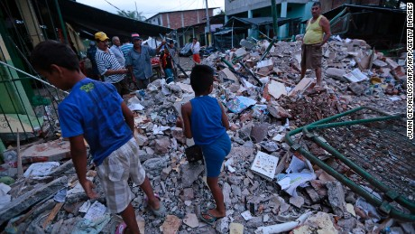 TOPSHOT - People stand amongst the rubble of fallen homes in Manta on April 17, 2016, after a powerful 7.8-magnitude earthquake struck Ecuador on April 16.  At least 77 people were killed when a powerful 7.8-magnitude earthquake struck Ecuador, destroying buildings and a bridge and sending terrified residents scrambling from their homes, authorities in the Latin American country said on April 17. / AFP / JUAN CEVALLOS        (Photo credit should read JUAN CEVALLOS/AFP/Getty Images)
