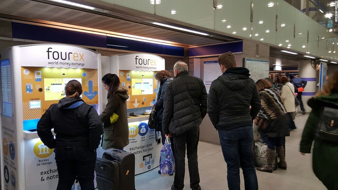Customers queue up to use Fourex's currency machines in London's King's Cross station.