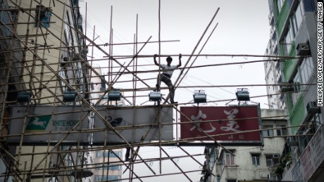A worker balances on a bamboo scaffolding above the streets in Hong Kong on March 20, 2014. Hong Kong's bamboo scaffoldings remain a common sight high above the streets of the city, scaling the sides of towering, ultra-modern steel and glass buildings on traditional bamboo poles linked through ancient design concepts.     AFP PHOTO / Philippe Lopez        (Photo credit should read PHILIPPE LOPEZ/AFP/Getty Images)