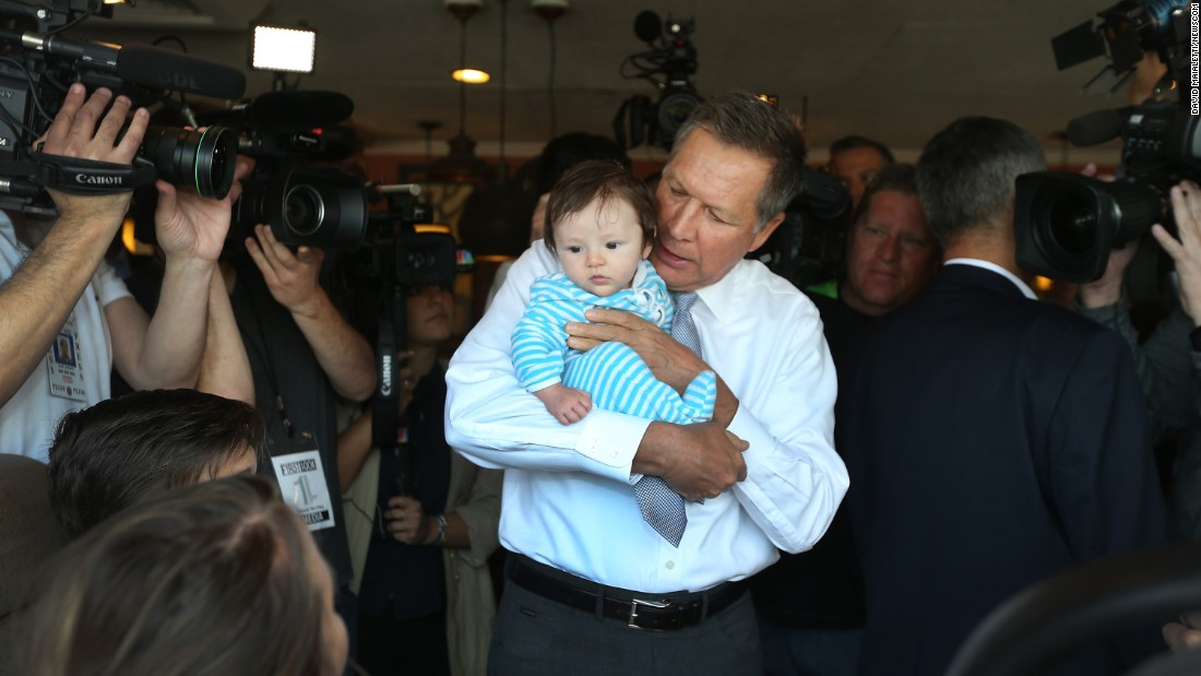 Ohio Gov. John Kasich, a Republican presidential candidate, holds an infant during a visit to a Philadelphia diner on Monday, April 25.