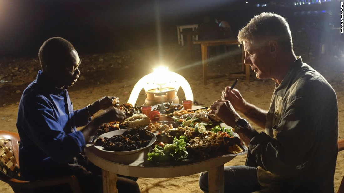 "Later that same night, Bourdain and Chef Pierre Thiam enjoy a seafood dinner in Dakar at Cour de Cassation Beach, one of Thiam's favorite beach shack ""restaurants."""