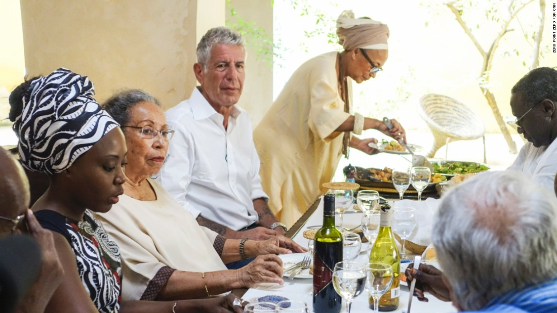 "Bourdain enjoys a garden party meal hosted by Marie-Caroline Camara (far right) at her bed and breakfast, ""Au Fil du Fleuve"" in Saint-Louis. Camara has worked to preserve some of the city's beautiful historic architecture."