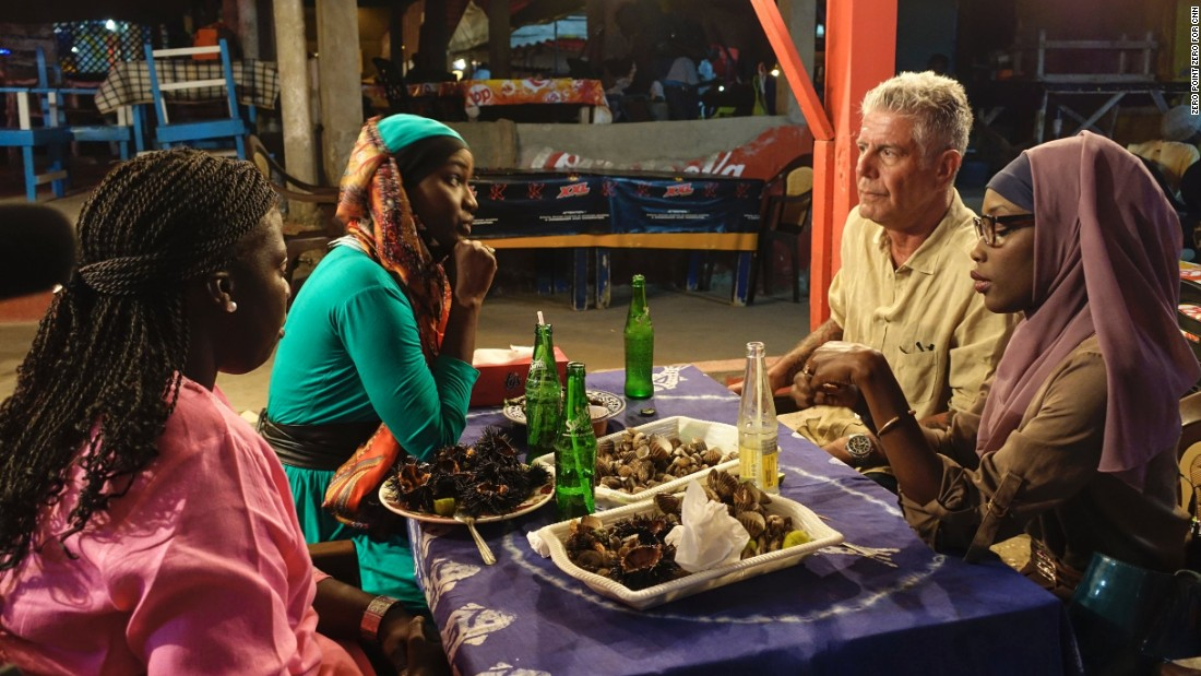 Bourdain shares clams and sea urchins with Oumy N'Dour, Fama Diouf (far left) and Minielle Tall (far right) at Vitres de Sokone in Dakar.