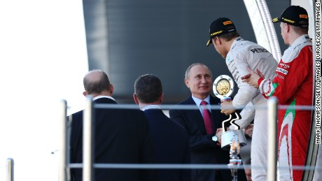 Rosberg is handed his winner's trophy by Russia president Vladimir Putin