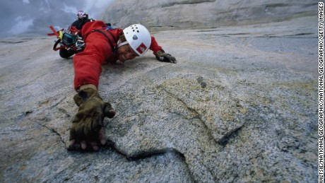 CANADA - JUNE 11:  Alex Lowe reaches up to feel which tool will hold his weight, Great Sail Peak, Baffin Island, Nunavut, Northwest Territories, Canada  (Photo by Gordon Wiltsie/National Geographic/Getty Images)