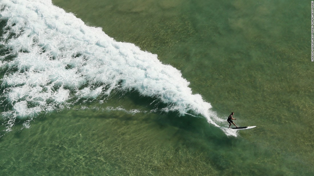 A stand-up boarder rides a wave at Manly Beach, one of Sydney's most popular beaches.