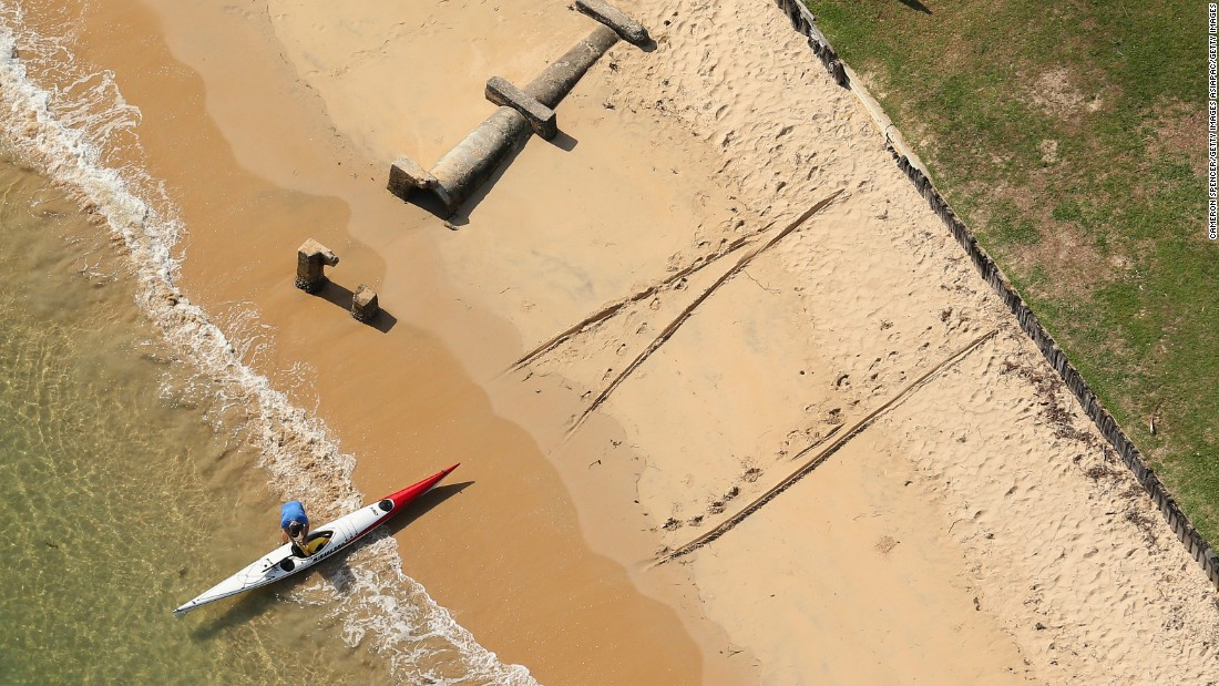 A kayaker prepares to launch his craft from the beautiful sands by the side of Pittwater.