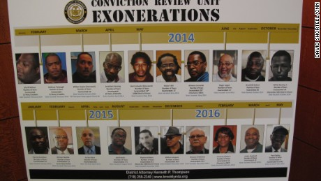 A posterboard in the Brooklyn District Attorney's office shows the faces of the 20 men and women who have been exonerated under Thompson's watch.