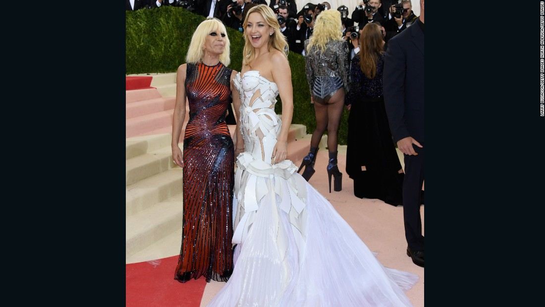Actress Kate Hudson is pictured wearing a dress by Versace, posing beside designer Donatella Versace.