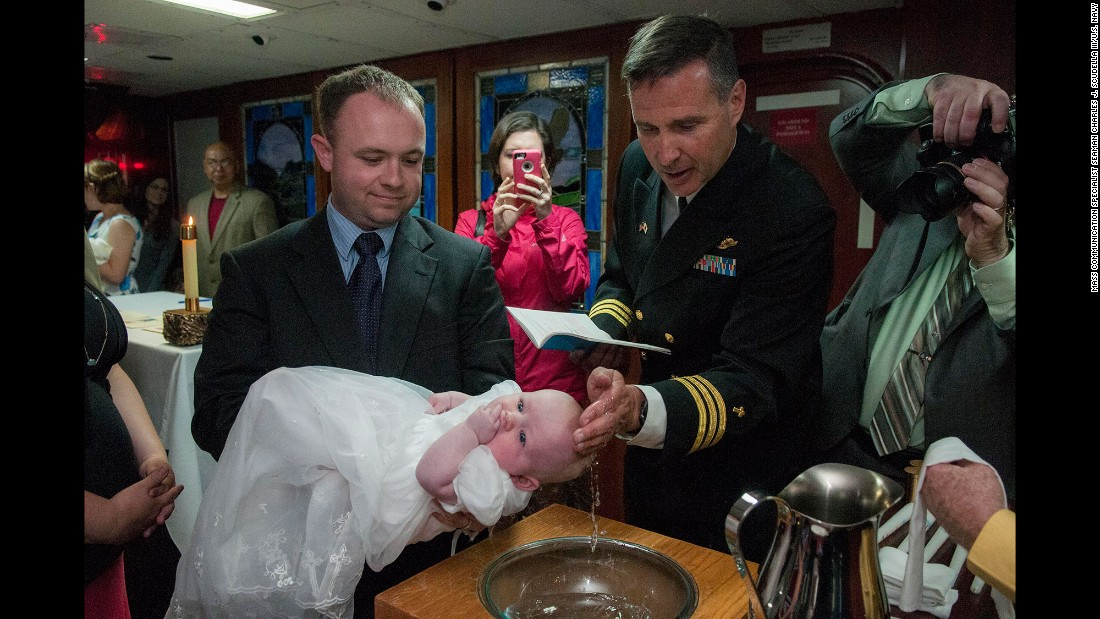 Cmdr. Joseph L. Coffey, a chaplain with the U.S. Navy, baptizes a child aboard the USS Ronald Reagan on Sunday, April 24. The aircraft carrier is docked in Yokosuka, Japan.