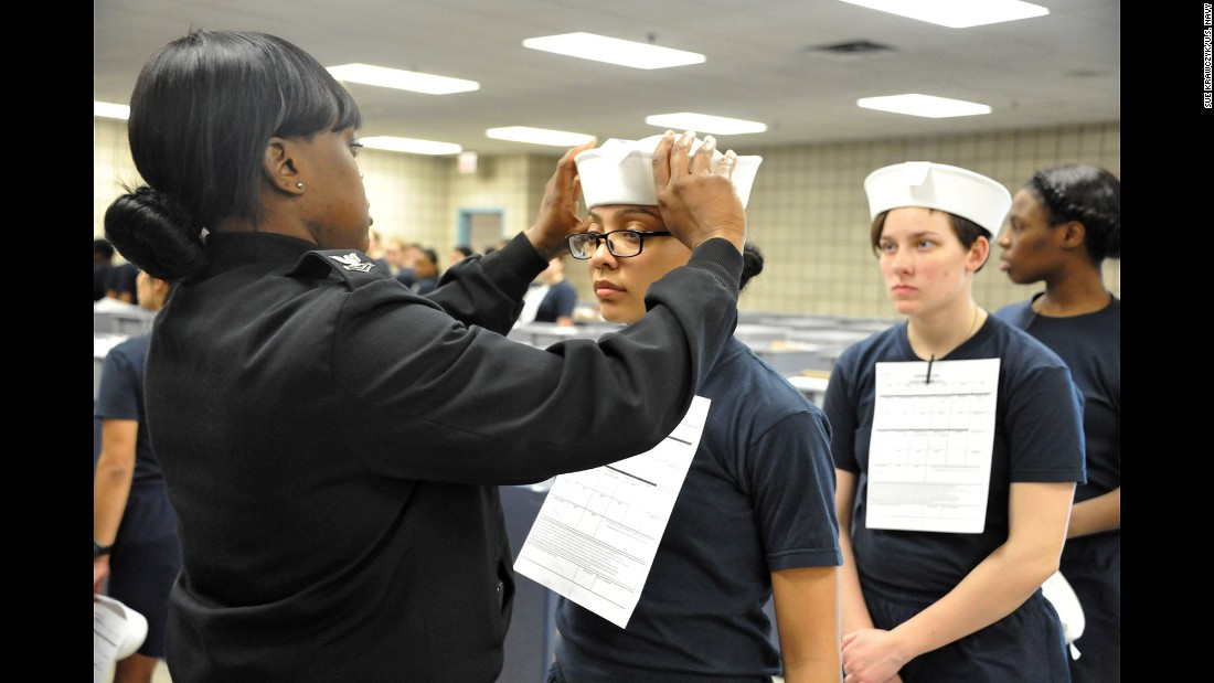"Engineman 2nd Class Shanice Floyd, a recruit division commander, ensures the proper fit of Megan Marte's hat during uniform issue Monday, April 4, in Great Lakes, Illinois. Marte was among the first female recruits to be issued the ""Dixie cup"" hat as part of the Navy's efforts at gender equality."