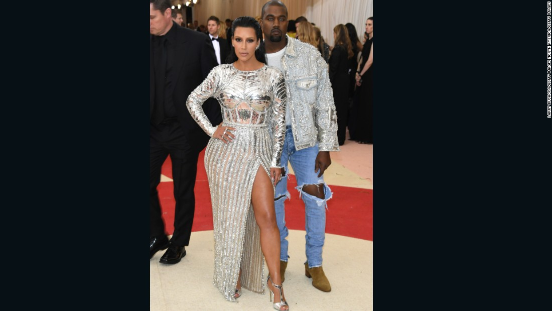 Kim Kardashian West is pictured here with husband Kanye West. The pair are both wearing outfits by Balmain, which Kanye West accessorized with blue contact lenses.