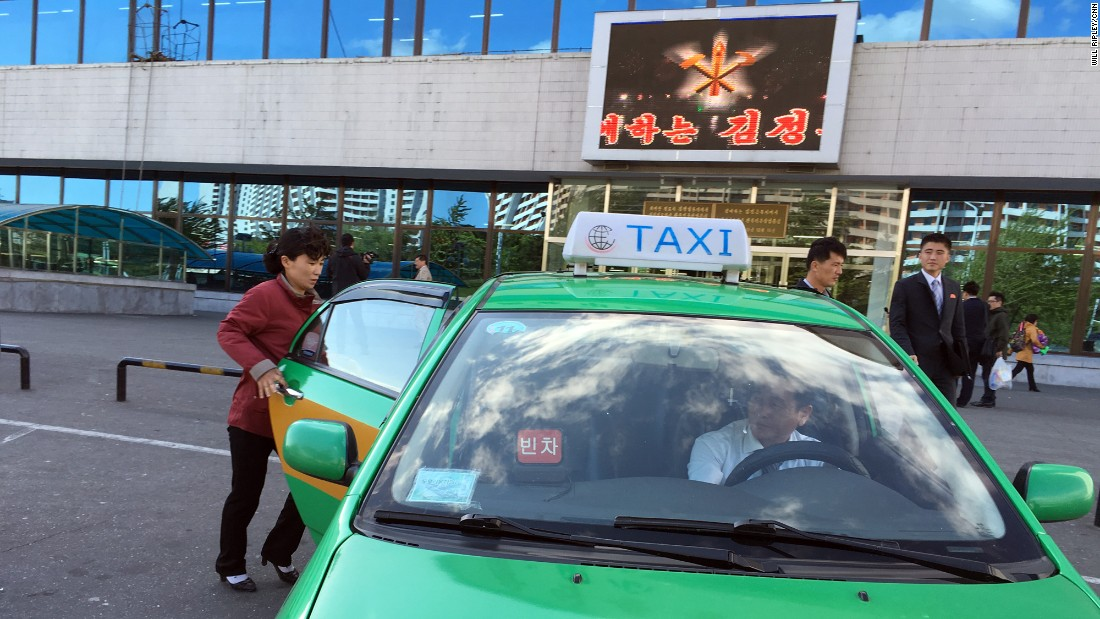 A woman gets into a taxi outside a new Pyongyang department store. The North Korean capital now has several taxi companies.