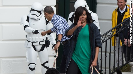 President Obama bumps fists with a Star Wars Stormtrooper as First Lady Michelle Obama waves to the crowd at the annual Easter Egg Roll at the White House in Washington, DC, on March 28, 2016.