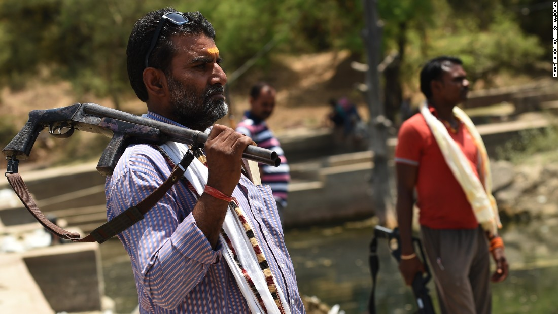 Gunmen stand alert at a water reservoir in Tikamgarh, India, on April 27.