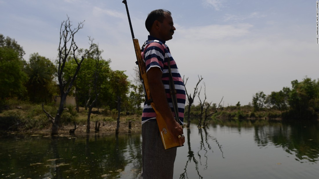 A gunman stands guard at a water reservoir in the central Indian state of Madhya Pradesh on Wednesday, April 27.