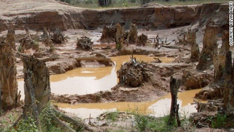 "A protected forest and river in Ghana, which is now strip mined for gold and saturated with mercury. Women and children carry tubs of sand and gravel for ""washing"" for gold."