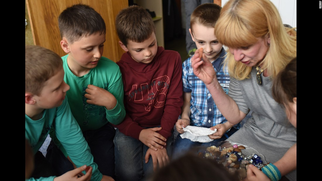 "A psychologist leads children taking part in a group ""sand therapy"" session at Promir Centre for Psychotherapeutic support in Slovyansk, eastern Ukraine."