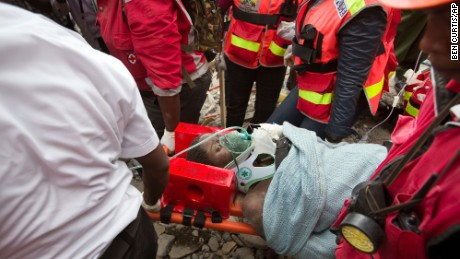 A woman is carried away on Thursday, May 5, in a stretcher by medics after she was pulled from the rubble of a collapsed building in Nariobi, Kenya. She was trapped in the rubble for six days.