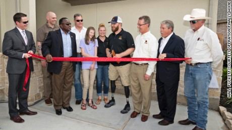 Cpl. Jonathan Dowdell (center) and his family cut the ribbon on a new home from Dan Wallrath (far right) and his nonprofit, Operation Finally Home.