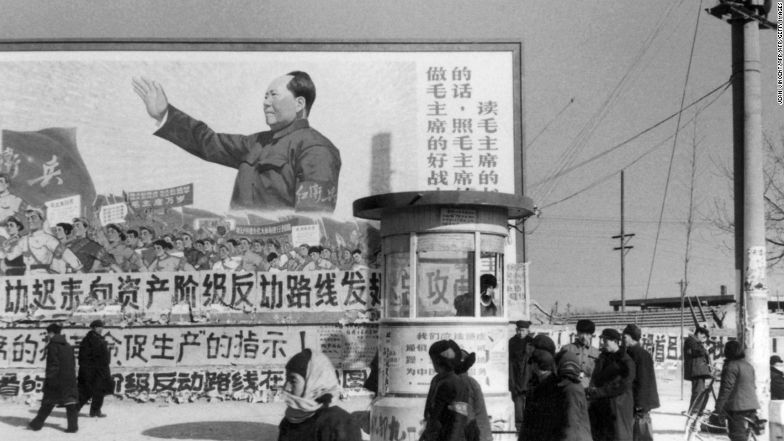 "Beijing residents walk past a huge poster of Mao during the Cultural Revolution. The poster calls on people ""to be good soldiers of Mao Zedong."""