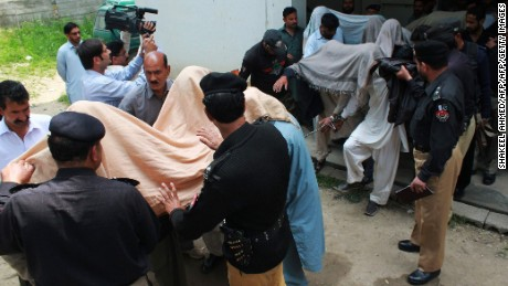 "Pakistani police escort suspects accused of killing and setting fire to a woman as they arrive at a court in Abbottabad on May 5, 2016.   A Pakistani woman was drugged, strangled and then her body set ablaze because she helped her friend elope, police said May 5, announcing the arrest of 14 people in a twist on the grim practice of ""honour killings"". / AFP PHOTO / SHAKEEL AHMEDSHAKEEL AHMED/AFP/Getty Images"