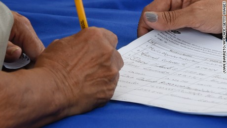 An anti-government demonstrator sign the form to activate the referendum on cutting President Nicolas Maduro's term short, in Caracas on April 27, 2016. Opponents of Venezuelan President Nicolas Maduro hope to hold a referendum on removing him from office as early as November, a leading opposition figure said Wednesday. The center-right opposition has started gathering signatures to launch the first step towards a referendum to get rid of the socialist leader, whom they blame for an economic crisis and rising unrest.  / AFP / JUAN BARRETO        (Photo credit should read JUAN BARRETO/AFP/Getty Images)
