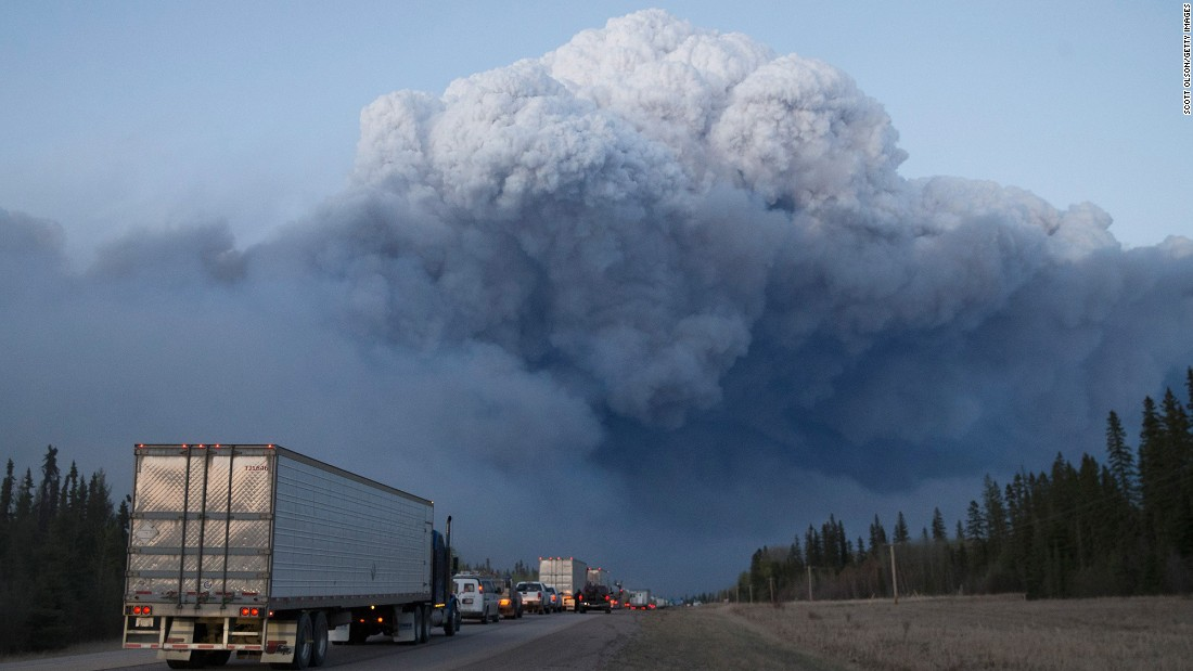 Drivers wait for clearance to take firefighting supplies into town on Thursday, May 5, outside Fort McMurray.