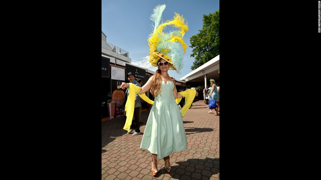 A fan shows off her feather-and flower adorned hat.