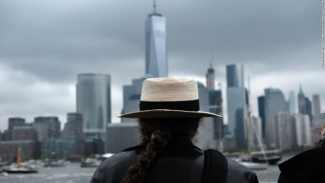 A man watches boats in New York Harbor from a vantage point in New Jersey as America's Cup racing begins Saturday.