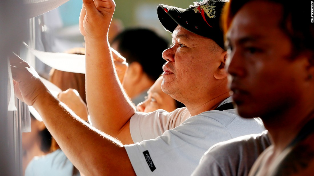 Filipino voters check the voters' list as they queue up to cast their choice for the presidential elections in Davao City in southern Philippines on May 9, 2016.