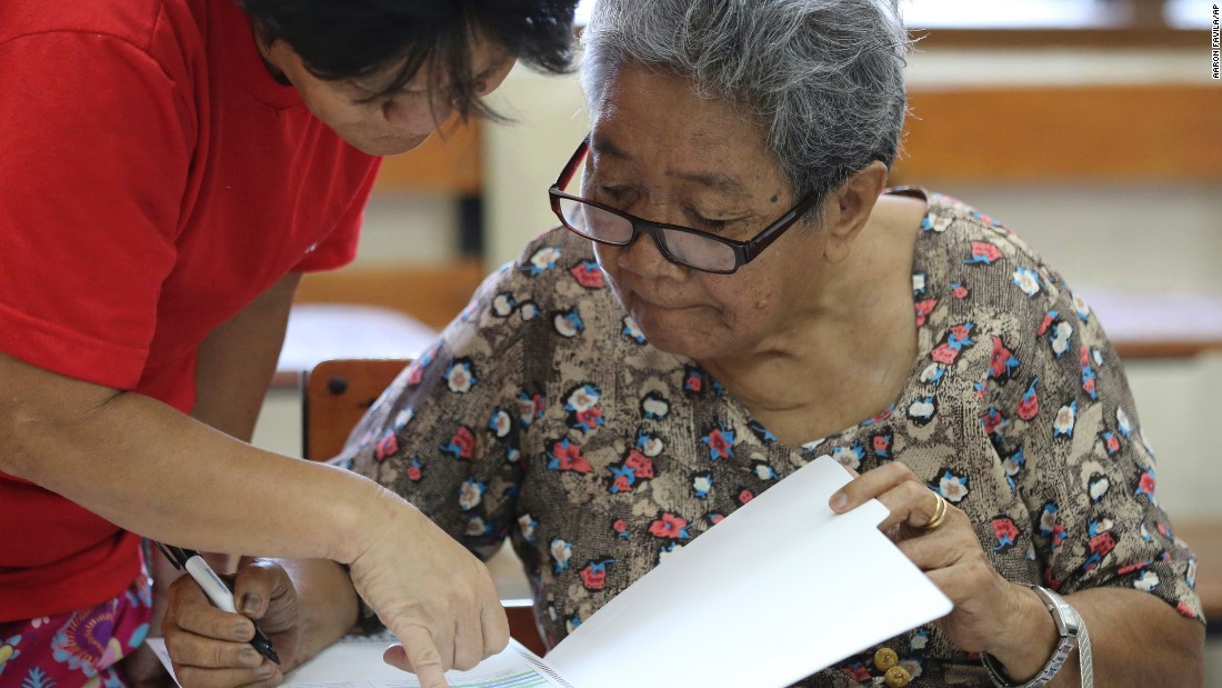 Eighty-year-old Dioleta Esteban is assisted as she votes at a polling center in suburban San Juan, east of Manila, Philippines on Monday, May 9, 2016.